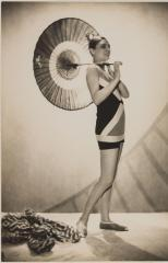 Profile model in geometrically patterned bathing suit holding an umbrella, by Lucien Lelong